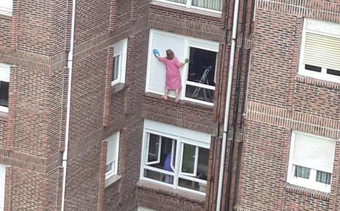 Mujer limpia cristales de un cuarto sin protección